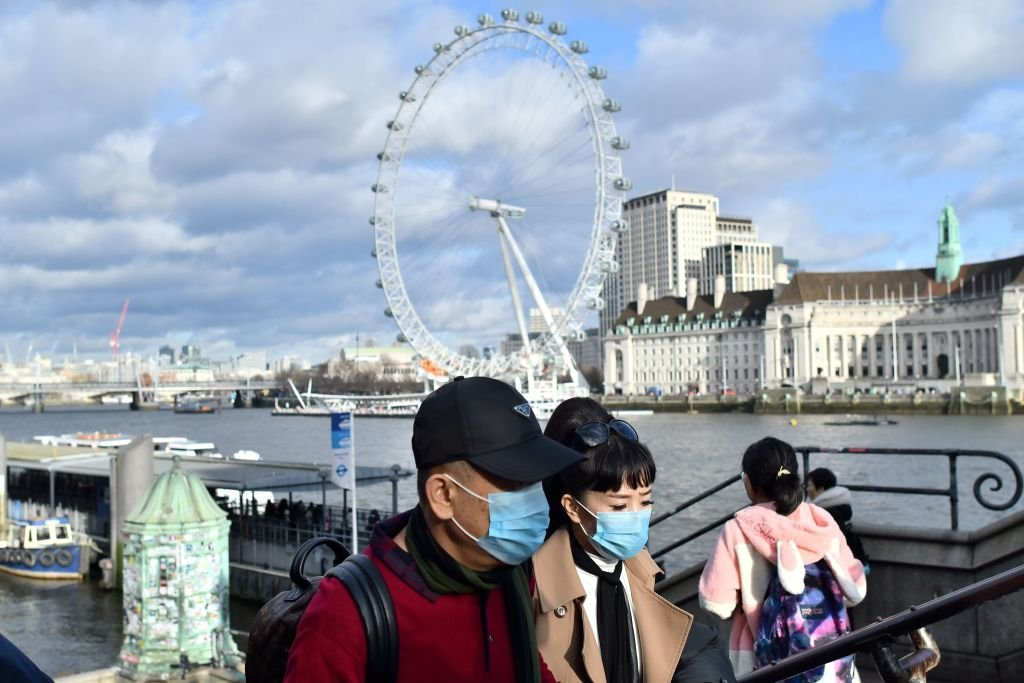 A couple wear face masks as they walk along the Thames embankment in central London