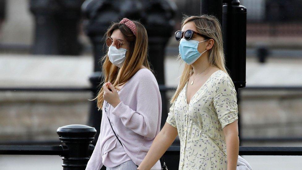 Two women walking wearing face masks