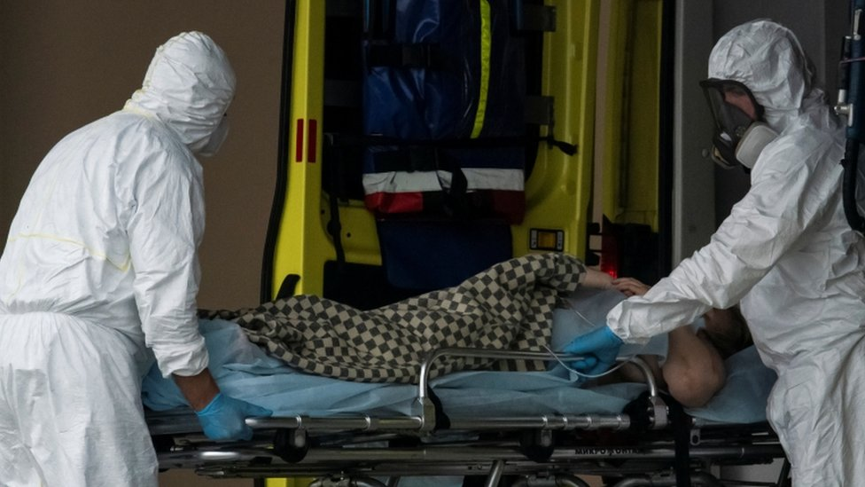 Medical specialists transport a person on a stretcher outside a hospital on the outskirts of Moscow on 12 May