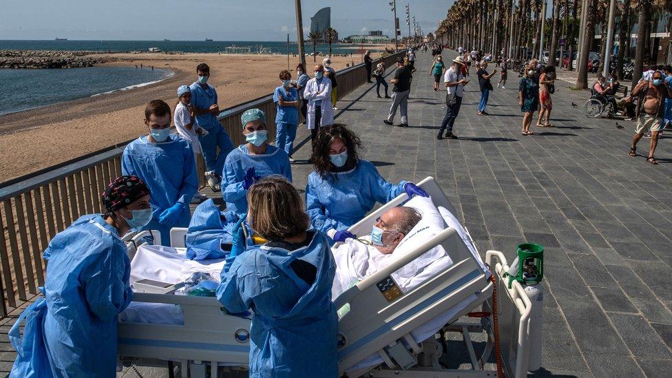 Pacijent leži u krevetu pored mora okružen medicinskim radnicima.