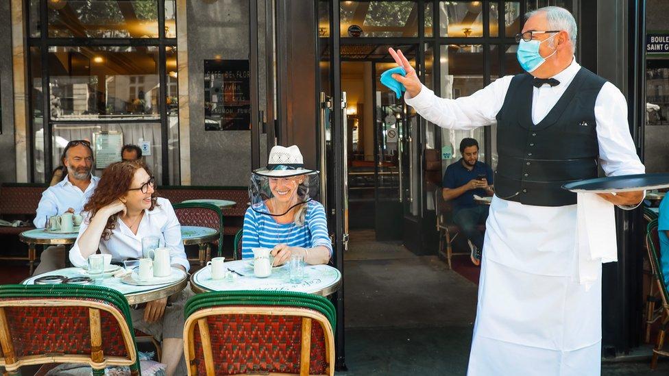 A waiter gestures towards customers in Paris