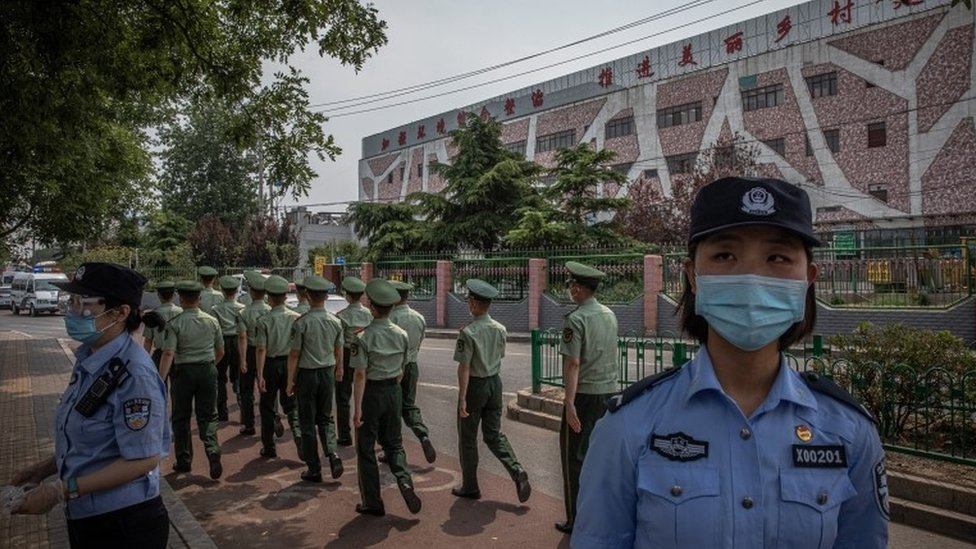 Chinese police officers wearing face masks stand guard next to the closed Xinfadi market building in Fengtai district, Beijing, China, 13 June 2020.