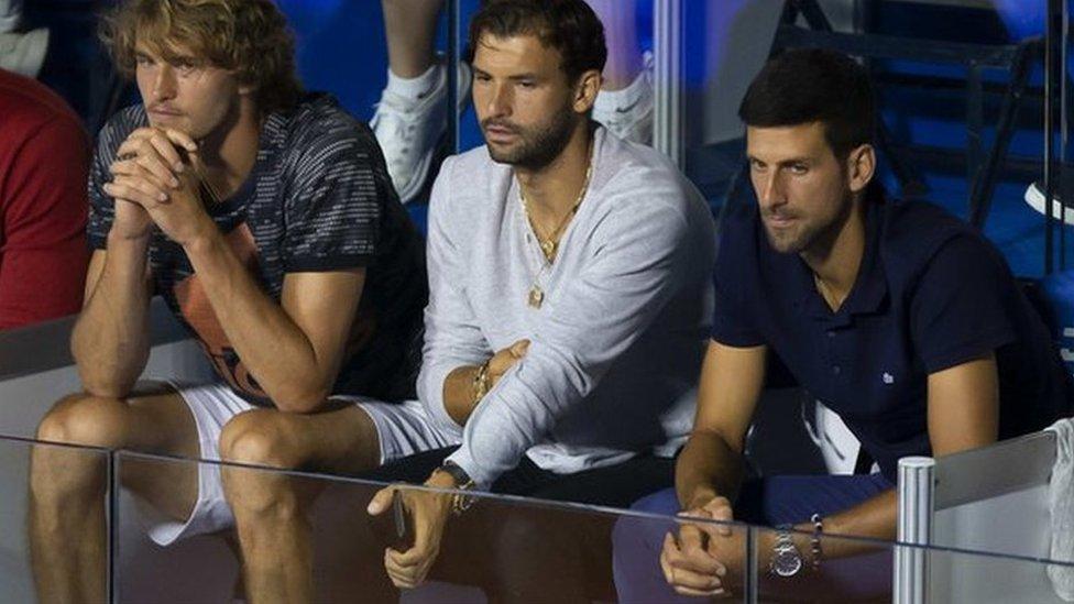 Grigor Dmitrov seated next to Novak Djokovic