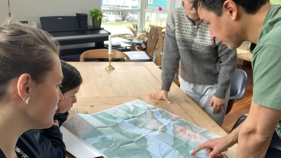 Arnakkuluk Kleist and her family look at a map