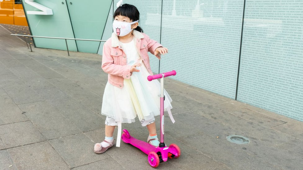 Small Chinese girl, wearing a mask, on a pink scooter going out and about