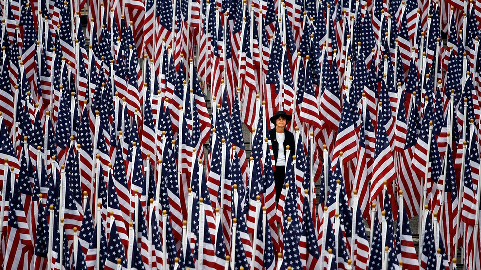 """A woman walks through some of the nearly 3000 United States flags that make up the """"Healing Field"""" outside the Pentagon during the dedication of the Pentagon Memorial September 11, 2008 in Arlington, Virginia."""
