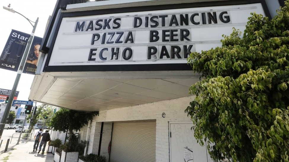 "A sign reading ""Masks Distancing Pizza Beer"" is displayed above a restaurant and bar on Sunset Boulevard amid the COVID-19 pandemic on June 29, 2020 in Los Angeles"