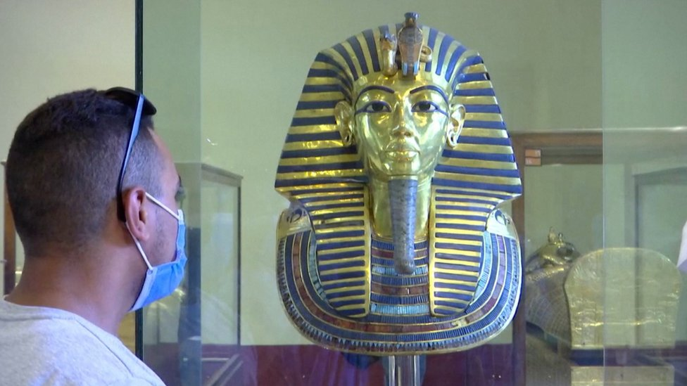 muškarac s maskom pred statuom kralja tutankamona u kairu