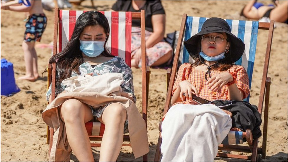 People on the beach with facemasks