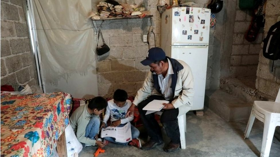 Facundo Martinez reviews school work with his children after a televised class as millions of students returned to classes virtually after schools were ordered into lockdown in March, due to the coronavirus disease (COVID-19) outbreak, in Chilcuautla, Hildalgo state, Mexico August 24, 2020.