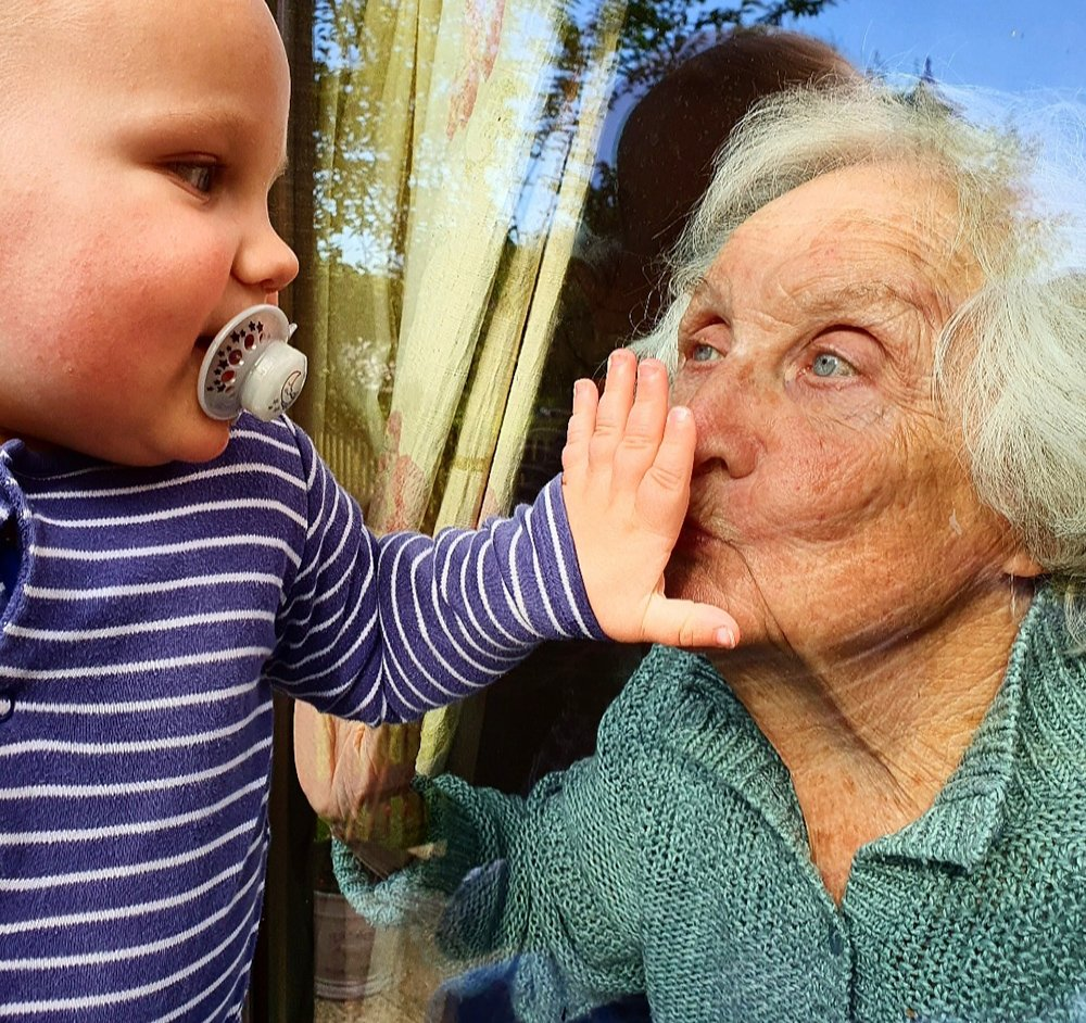 Young child and his great grandma greet each other through the window pane