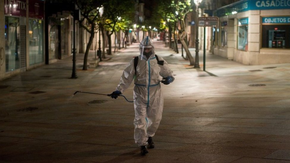 A local cleaner disinfects parts of Barcelona