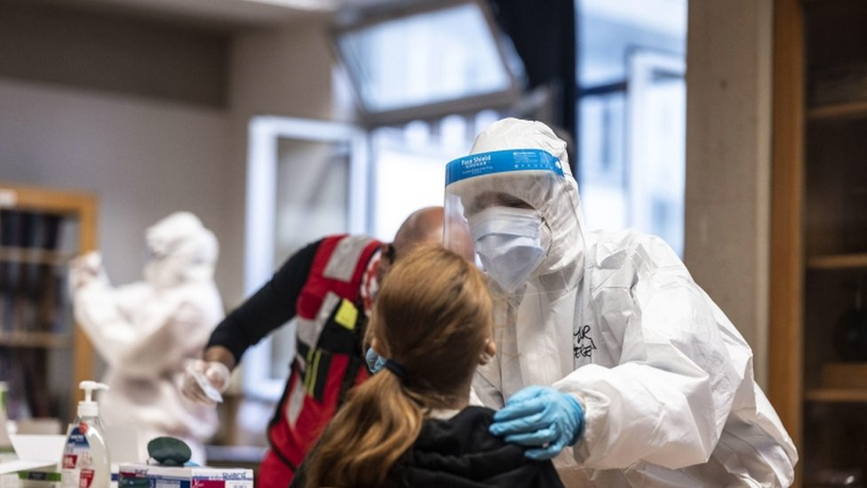 A health worker wearing overalls and a protective mask performs a swab test on a student in Florence, Italy