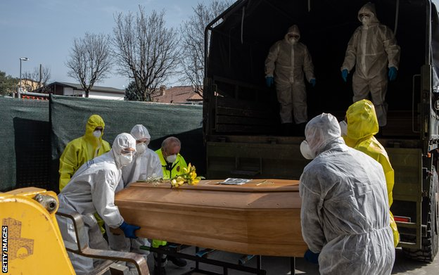 Carabinieri officers, wearing protective suits, lift a coffin on March 28, 2020 in Ponte San Pietro, near Bergamo