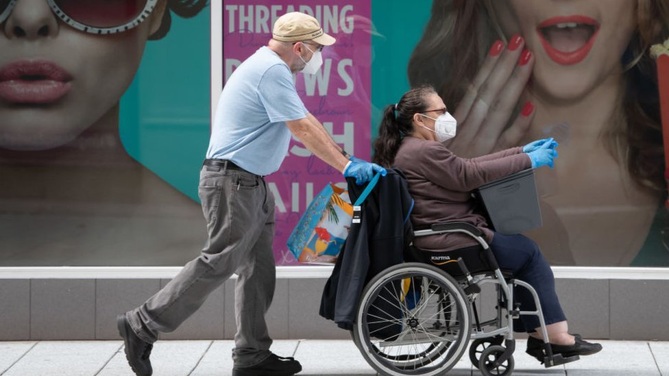 A woman sitting in a wheelchair wearing a mask, with a man in a mask pushing the chair