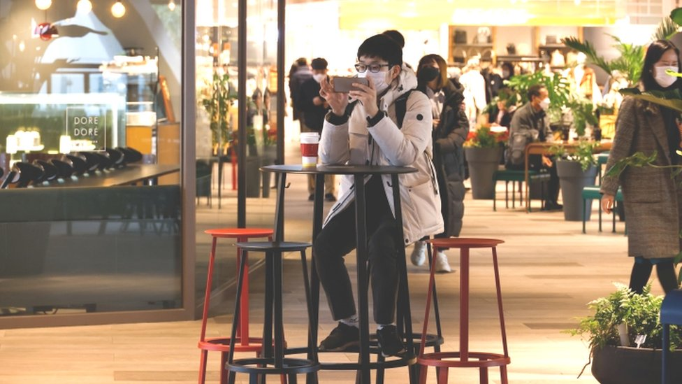 Man uses mobile phone in shopping mall in Seoul - 2 December