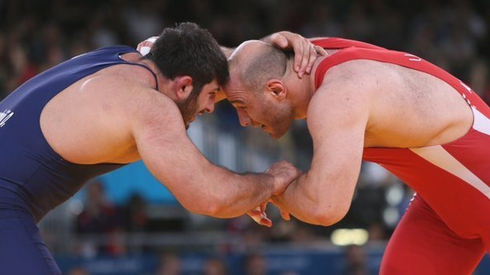 Uzbekistan's Artur Taymazov (R) wrestles Georgia's Davit Modzmanashvili in their Men's 120kg gold medal match at the London Olympics