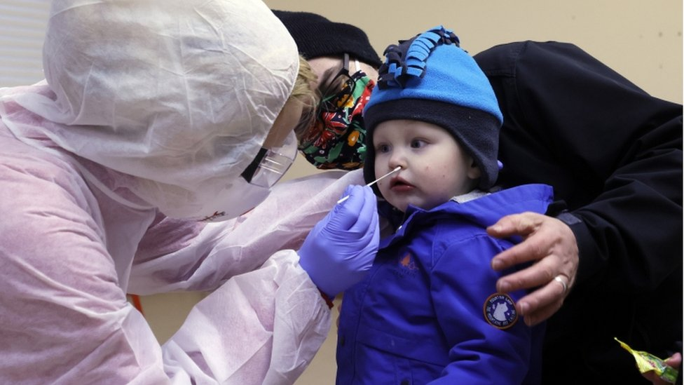 A health worker takes a swab from a child during a test in a coronavirus test station in a playschool in Hildburghausen, Germany, 01 December 2020