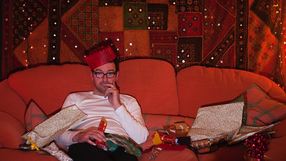 Man on couch wearing Christmas hat