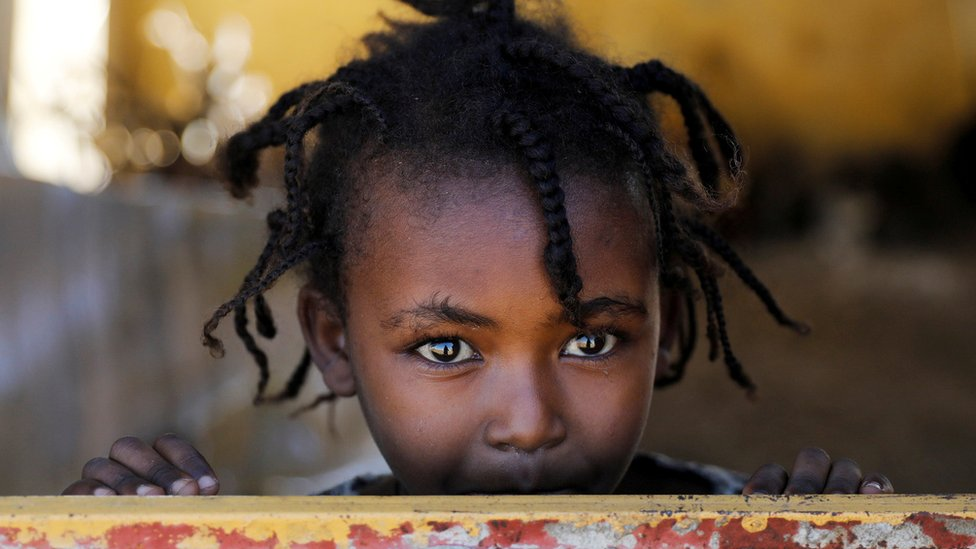 An Ethiopian girl stands at the window of a temporary shelter, at the Village 8 refugees' transit camp, which houses Ethiopian refugees fleeing the fighting in the Tigray region, near the Sudan-Ethiopia border, Sudan, December 2, 2020