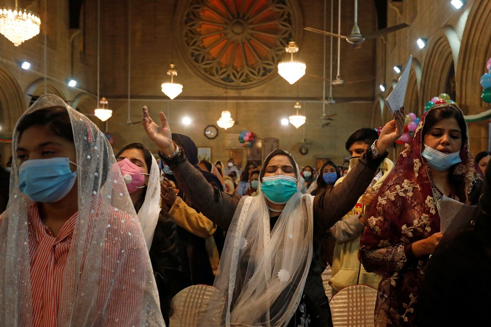 Women wear face masks as they pray during a Christmas Eve Mass in St Andrew's Church in Karachi, Pakistan. Photo: 24 December 2020