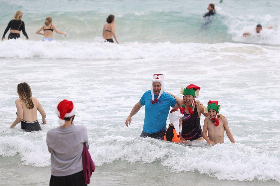 People wear Christmas-themed attire at Bondi Beach in Sydney, Australia. Photo: 25 December 2020