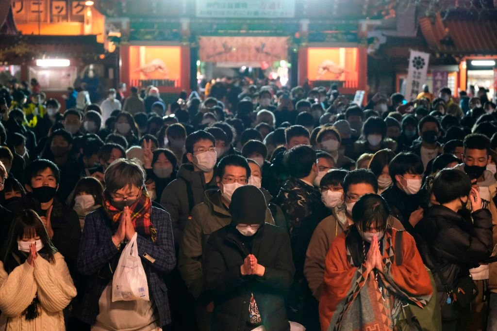 Wearing masks, people in Tokyo visit the Shinto Kanda Myojin Shrine to mark the new year