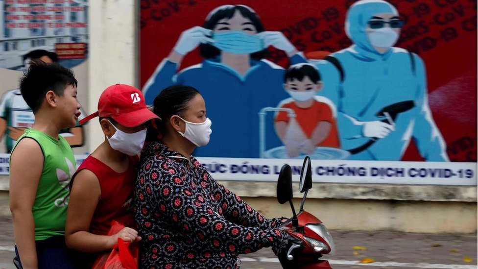 A woman wears a protective mask as she drives past a banner promoting prevention against the coronavirus disease (COVID-19) in Hanoi, Vietnam July 31, 2020.