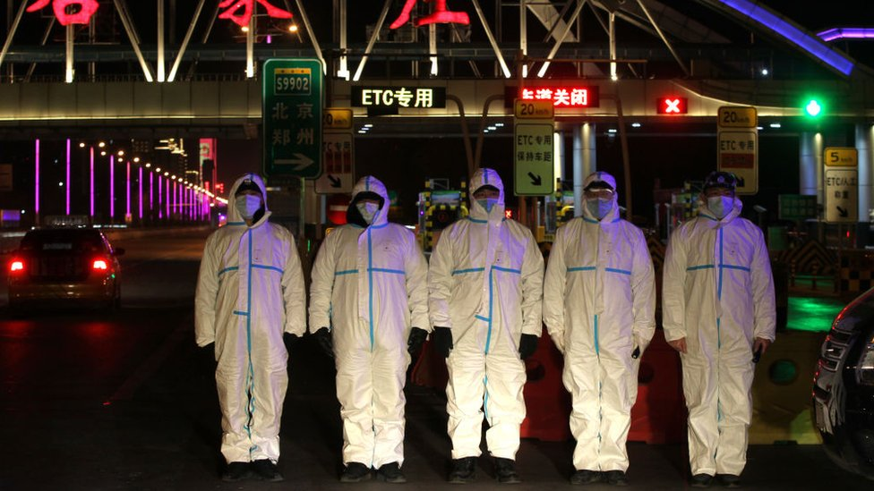 Police wearing protective suits block a road in the Chinese city of Shijiazhuang, January 2021