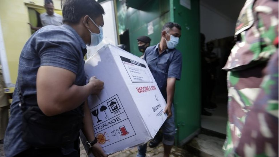 """Workers unload boxes containing a COVID-19 vaccine from a truck to a storage building, upon the arrival of Sinovac""""s COVID-19 vaccine in Banda Aceh, Indonesia, 12 January 2021. I"""