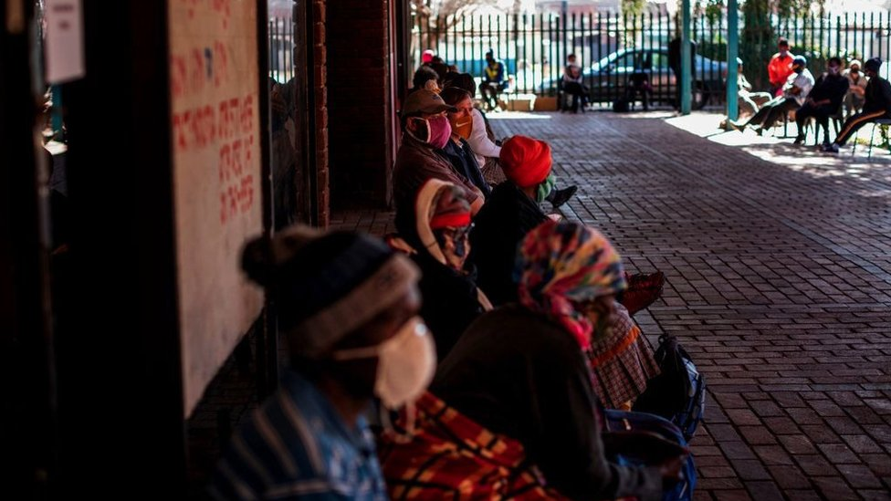 People queue to receive food parcels distributed by Meals on Wheels in Brapkan, South Africa, on July 6, 2020.