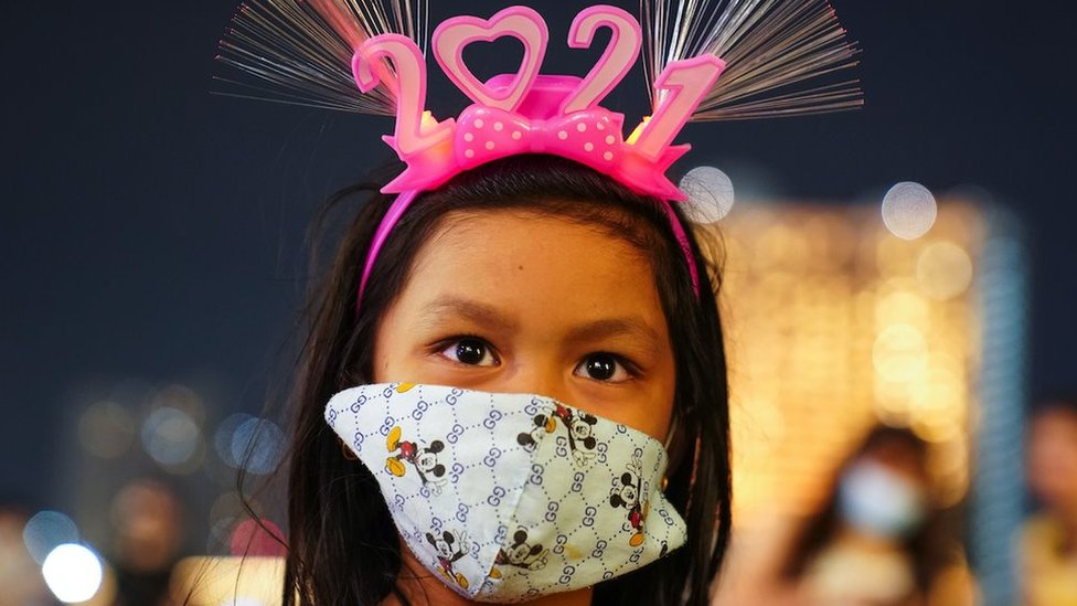 """A young woman wearing a protective facce mask and """"2021"""" head band looks on at a shopping mall as The New Year countdown celebrations in Bangkok"""