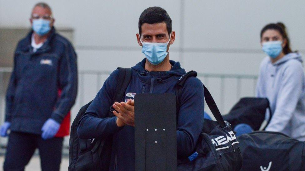 Novak Djokovic wearing a mask at Adelaide Airport on his way to hotel quarantine