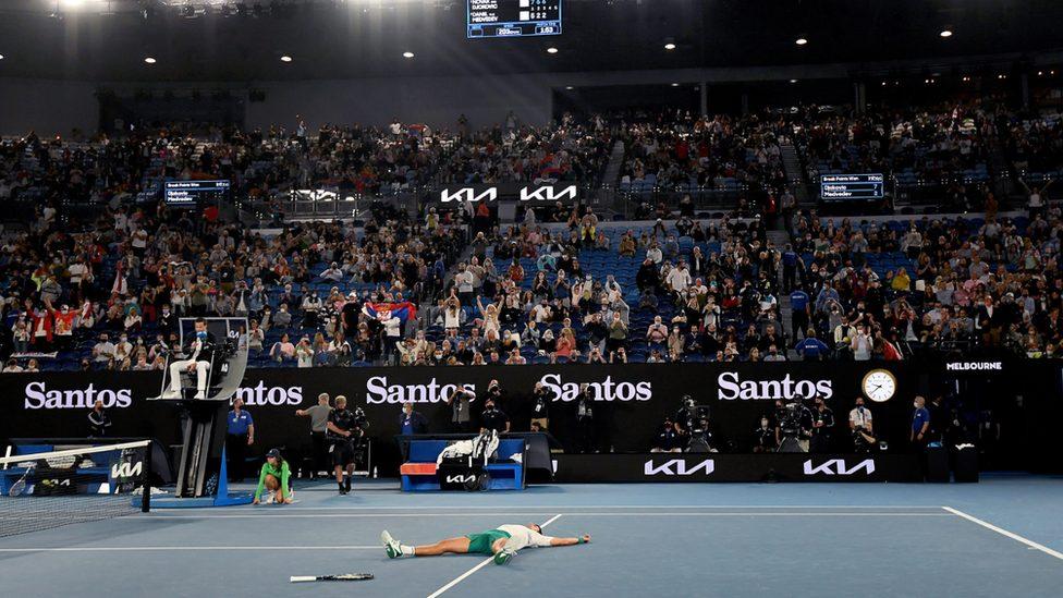 Crowd of tennis spectators cheer on Novak Djokovic after his winning point in the Australian Open 2021 grand final