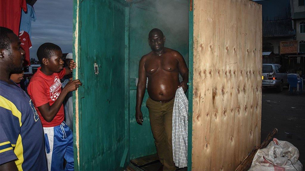 A man leaves a steam inhalation booth in Dar es Salaam, Tanzania, on 22 May, 2020