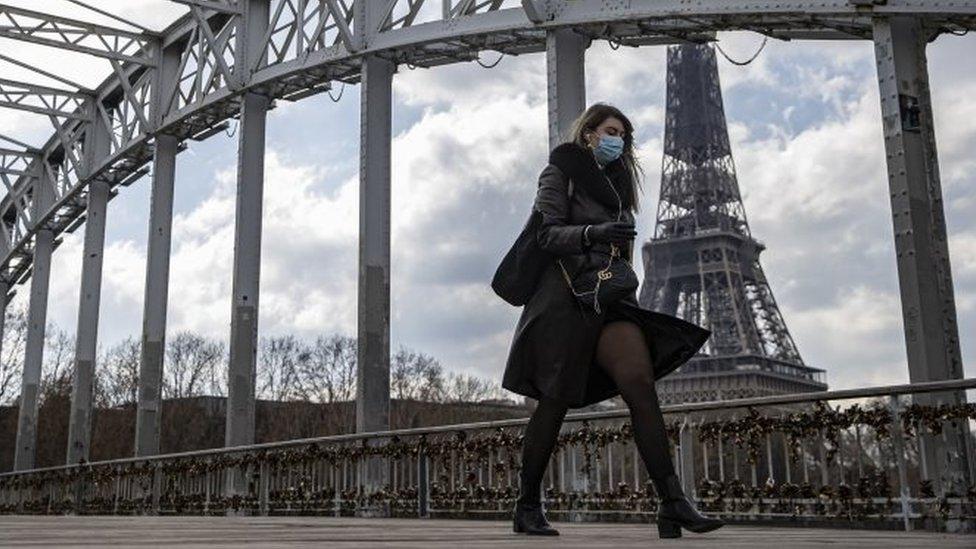 A woman wears a face mask as walks across a footbridge near the Eiffel Tower in Paris, France. Photo: 19 March 2021