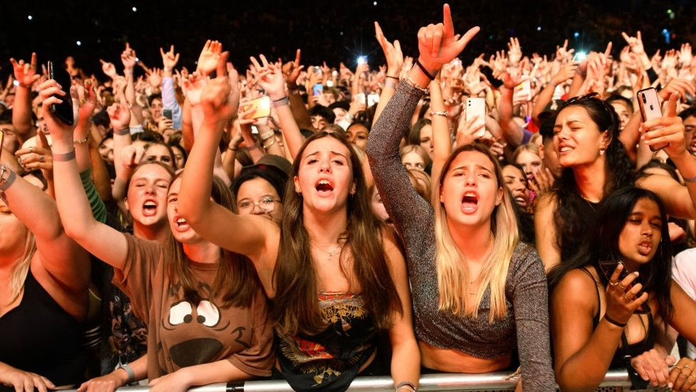 Young women cheering in the crowd at a music event