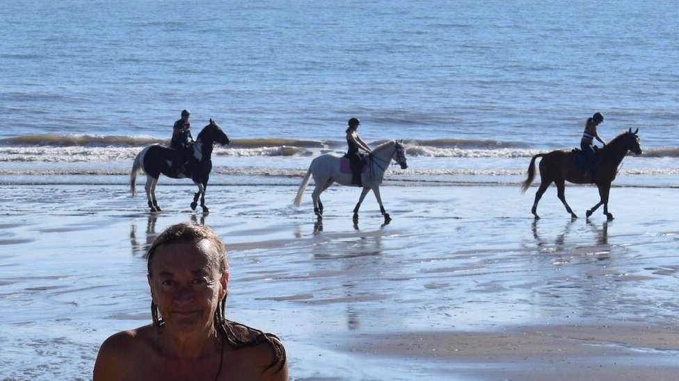 Donna standing naked on the beech with three people riding horses behind her