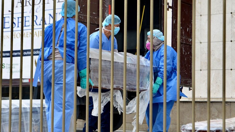 Morgue workers in Ecuador carrying a coffin wrapped up in plastic due to Covid-19