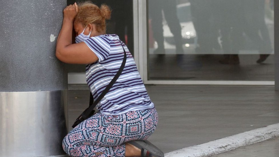 A woman on her knees, crying.