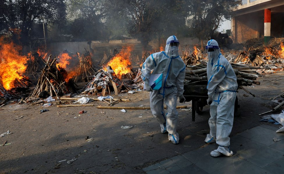 Health workers carry wood for funeral pyres in New Delhi, India