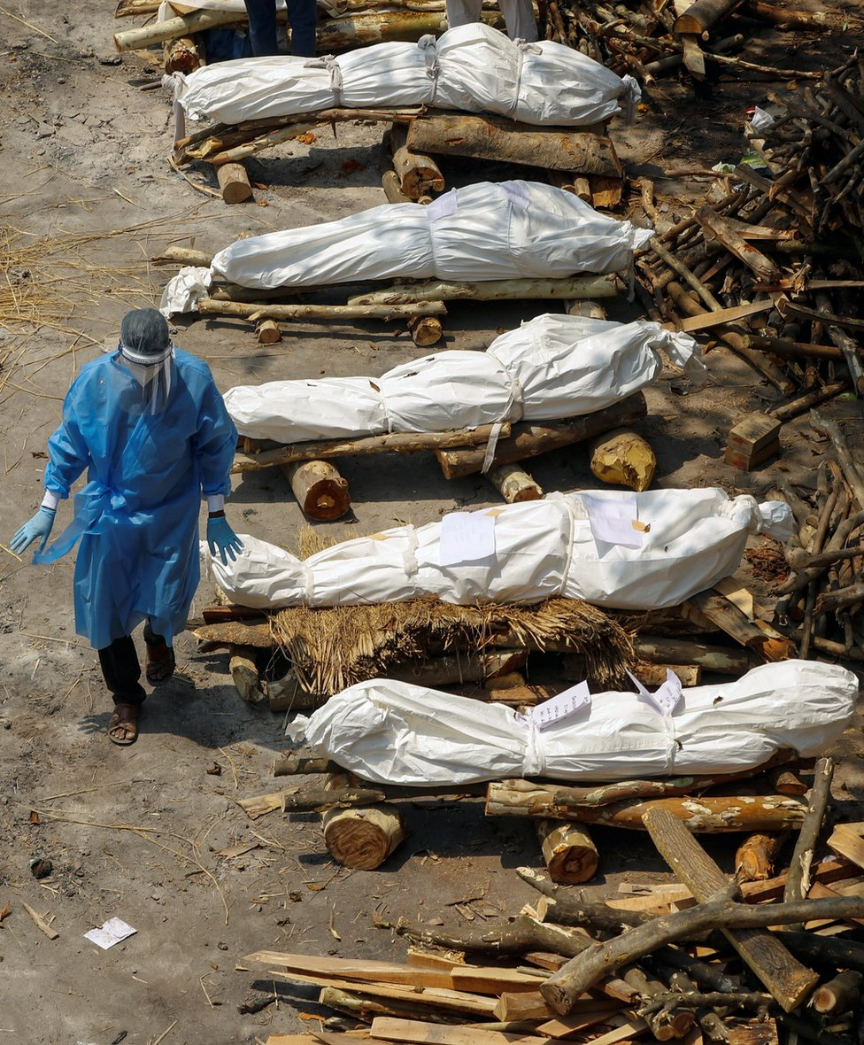 A health worker wearing personal protective equipment (PPE) walks past a row of wrapped bodies of Covid victims lying on prepared funeral pyres in New Delhi, India