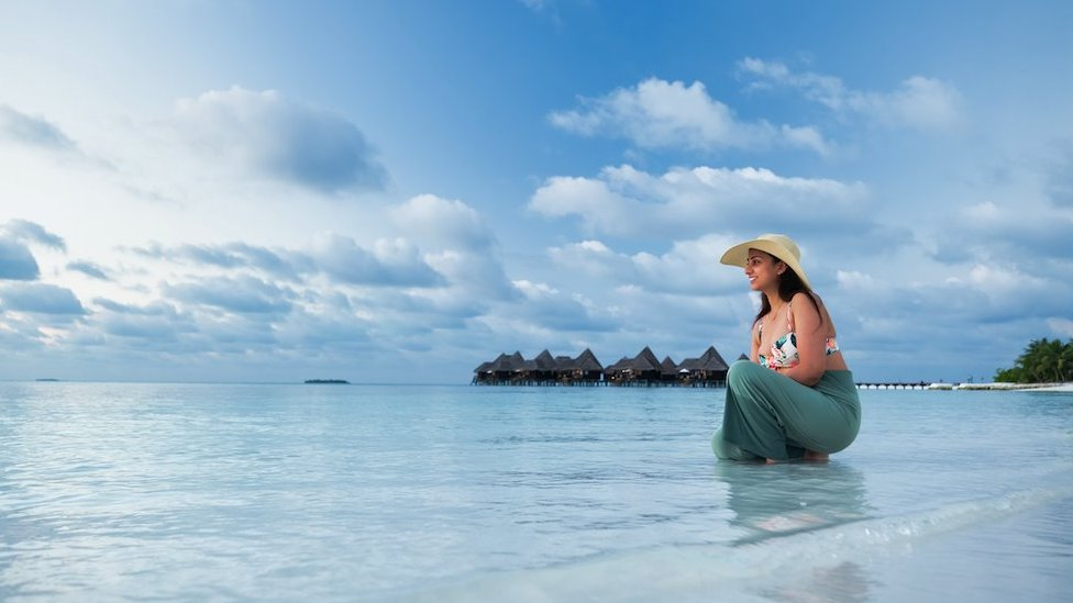 A woman enjoying the blue sea in an afternoon in the Maldives - stock photo