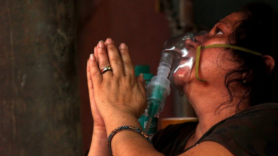 A woman with an oxygen mask on prays