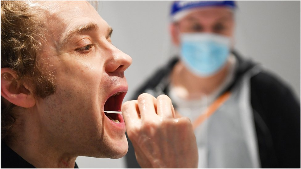 A man puts a swab in his mouth