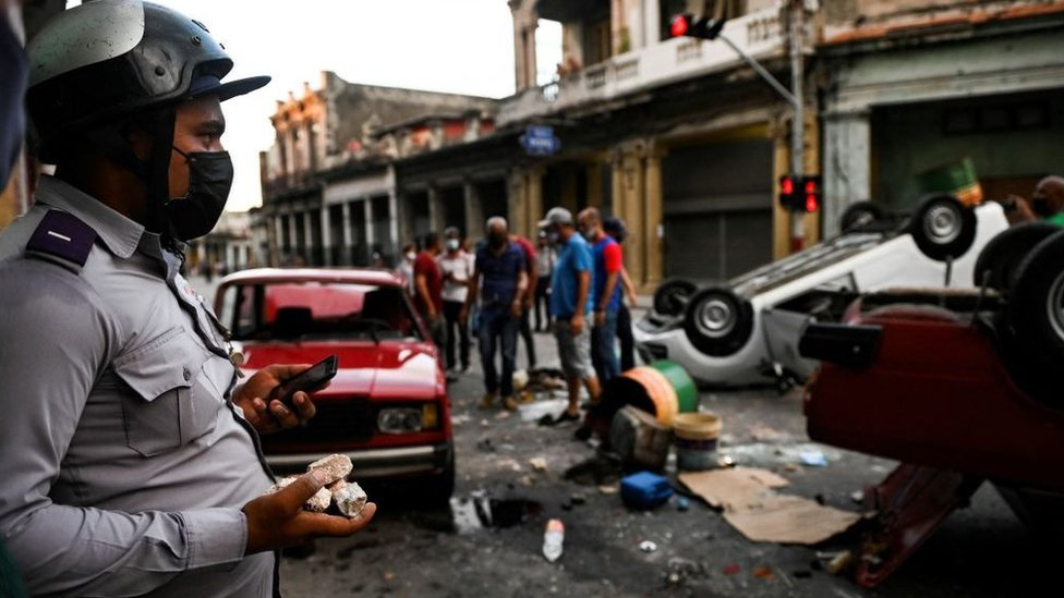 Police officer stands by as protesters overturn police vehicle, Cuba (11 July)