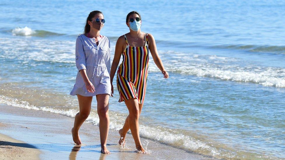 Women walking on a beach wearing face masks in Pensacola, Spain