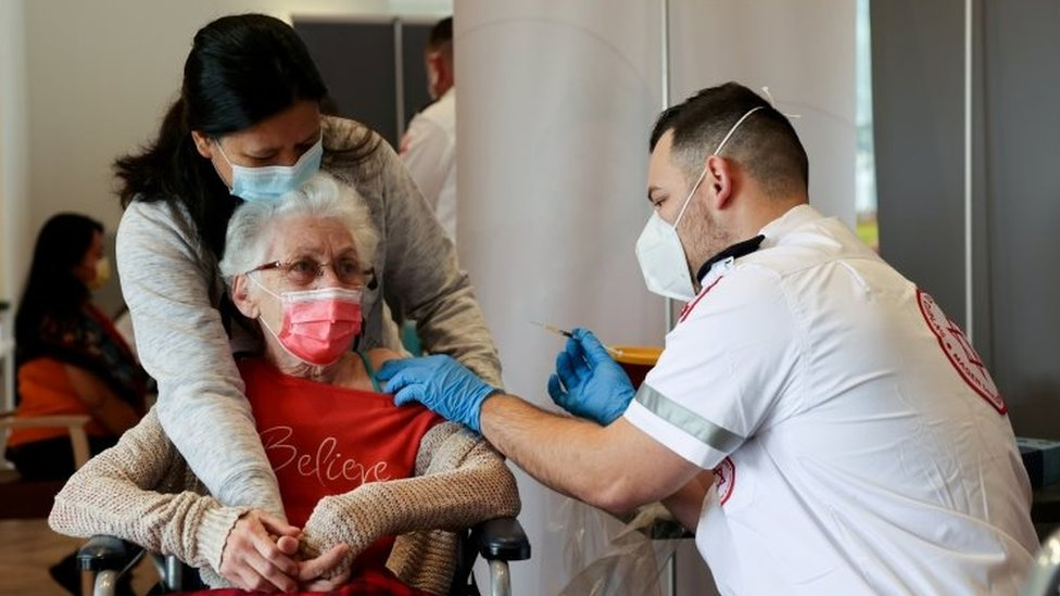 An elderly woman (centre) is vaccinated in Netanya, Israel. File photo