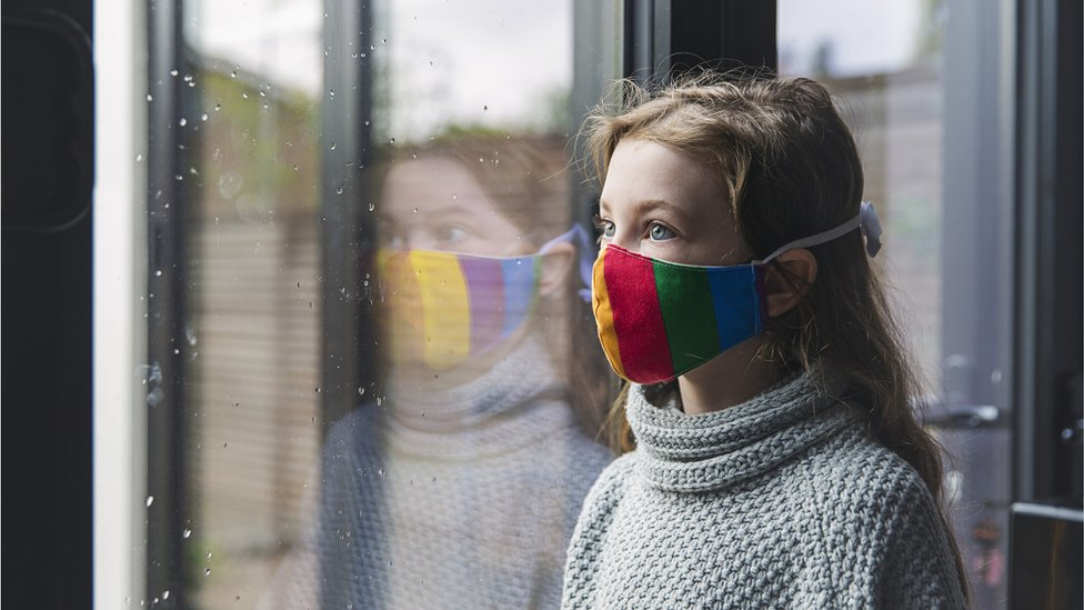 Girl wearing mask stands at a window